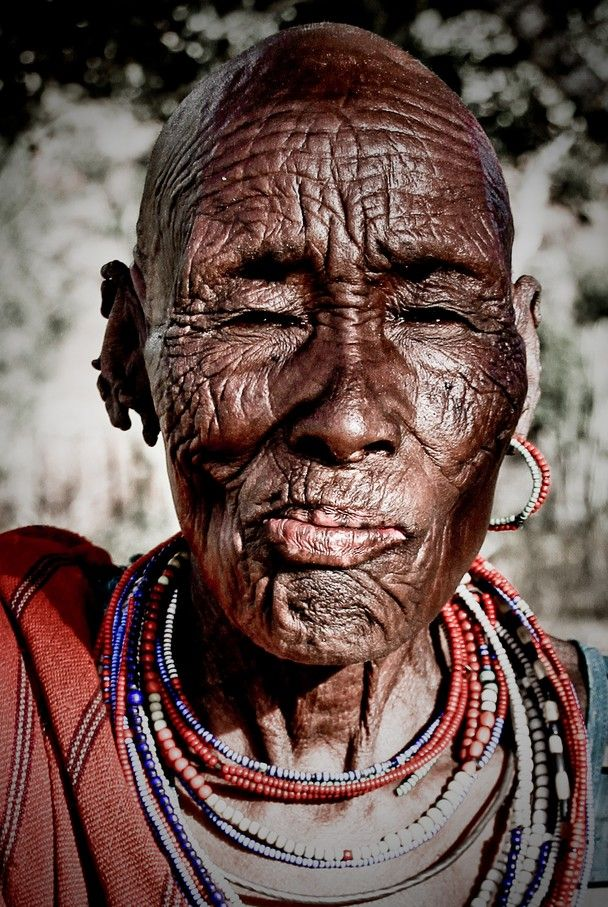 "Maralal, Northern Kenya. This photo of an old Samburu woman was taken in the outskirts of Maralal in Northern Kenya. I am still captivated by her gentle smile and the thousand stories told through her face. Asking her about her age, all she could tell was, that she was born in the year after the big drought. ""But age doesn't matter"", she says. What matters is to have enough children, in order to keep a large herd of cattle. Cause when the next drought comes, you'll better have enough cattle to survive, says the mother of 14 children...."