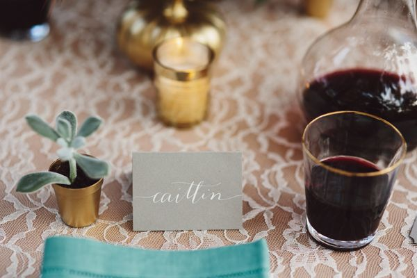 at each place setting: baby succulent + white calligraphy name card + napkin atop plate