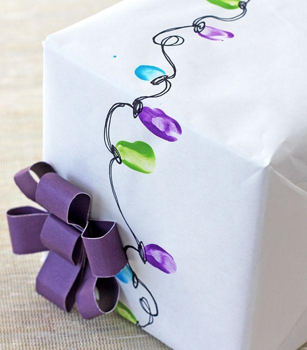 Kids fingertips in paint to make Christmas lights design gift wrap