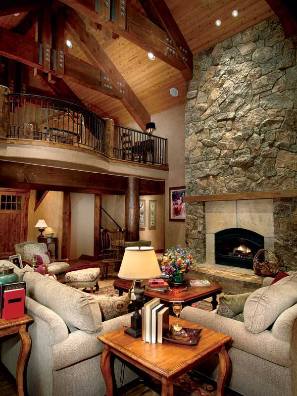 Massive timber trusses and stocky round log posts bring the beauty of wood to the lovely great room. A soaring stone fireplace warms the house on snowy days.