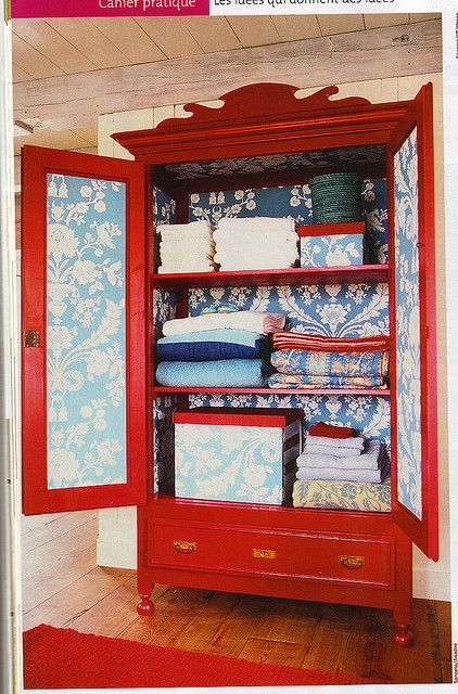 Farrow & Ball St Antoine wallpaper in blue & white, lines this bright red linen-press.