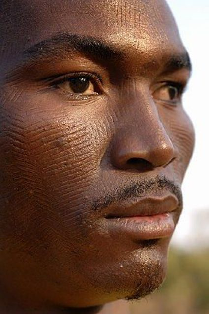 Africa | A man shows the scarifications on his face. Scarification is used as a form of initiation into adulthood, beauty and a sign of a village, tribe, and clan. Natitingou, Benin | © Jean-Michel Clajot