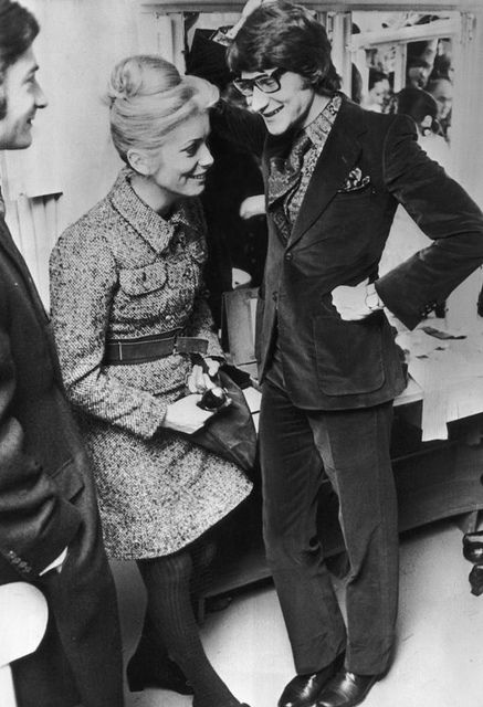 Catherine Deneuve with French fashion designer Yves Saint-Laurent backstage at one of Saint- Laurent's fashion shows, Paris, 30th January 1968. (Catherine wearing a model by Yves Saint Laurent).