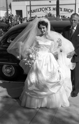 """Unpublished. Just 18 years old, Elizabeth Taylor arrives to marry hotel heir Conrad """"Nicky"""" Hilton at the Bel-Air Country Club. This was the first of her eight marriages, and for the occasion she wore a gown given to her by MGM Studios"""