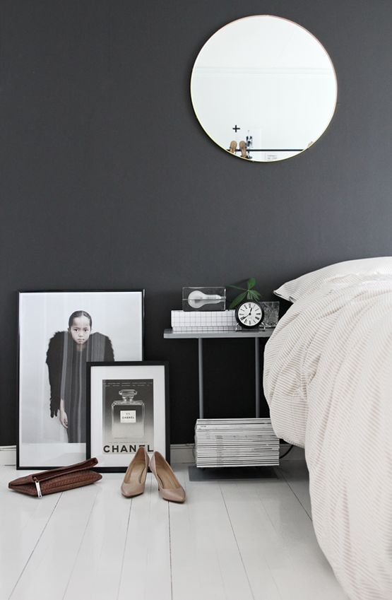 Charcoal walls. Round mirror. White floors. Art.