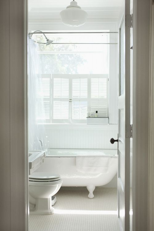 This bathroom, with its salvaged clawfoot tub, is a vision in white. See the full home tour here at Sneak Peek: Alexandra Grablewski and Todd Bonne.