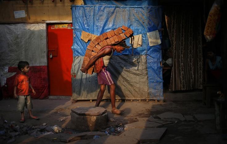 Un lavoratore Ripara Una casa danneggiata a Nuova Delhi, in India.  (Saurabh Das, Ap / Lapresse)
