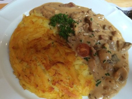 white plate with sauced mushrooms and yellow potato