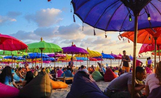 Se détendre sur la plage sur des poufs en regardant le coucher de soleil boire et manger en écoutant des bandes pla (301989059)