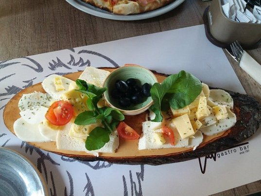 a wooden chase board with a selection of cheeses, tomatoes and arugula