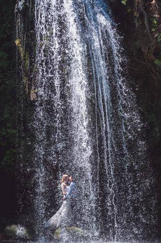 Les mariés derrière une chute d'eau
