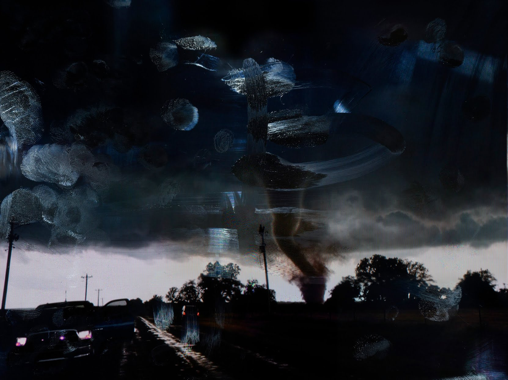 A tornado in an ominously dark sky.