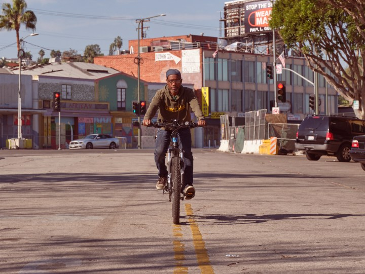 Adé rides his bike down the center of a Los Angeles street.