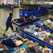 File photo of an employee working at a Goodwill in Toronto, Canada (© Steve Russell/Toronto Star via Getty Images)