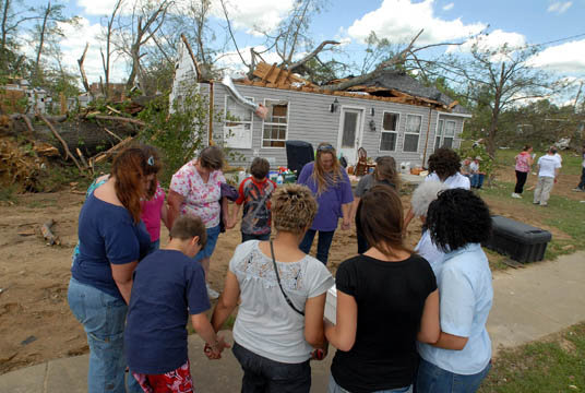 Residents gather in a prayer circle in front of Nancy Brooks' home. She was asleep when a large tree limb narrowly missed hitting her bed.