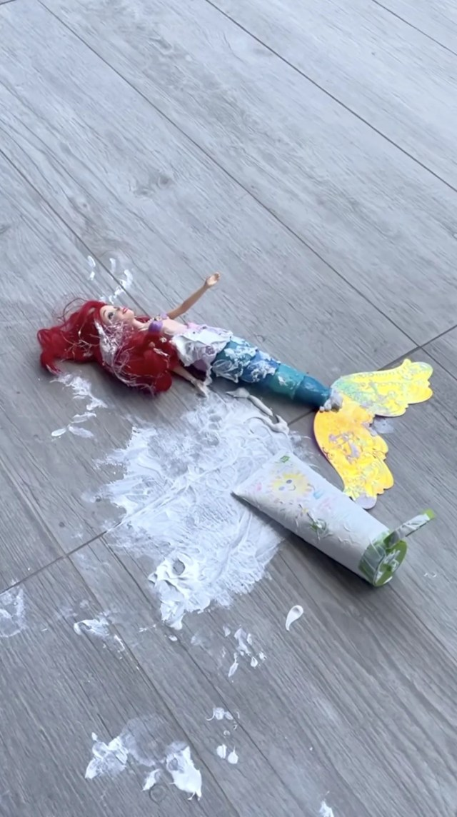 A Little Mermaid doll lying on the ground next to spilled sunscreen