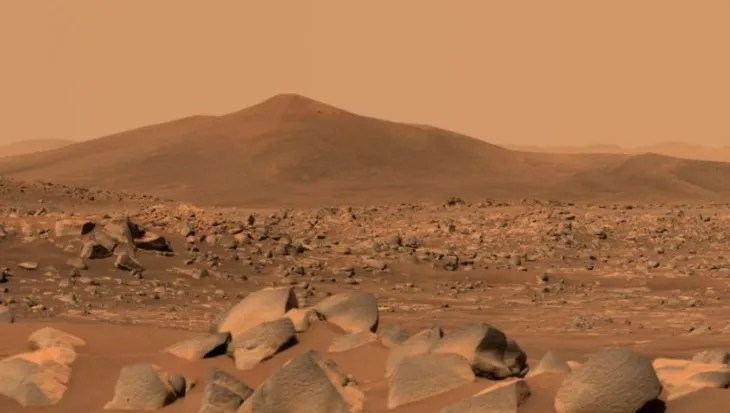 This image shows Santa Cruz, a hill located about 2.5 km from the rover.  The whole scene is inside the Jezero crater on Mars;  the rim of the crater can be seen on the horizon line beyond the hill.
