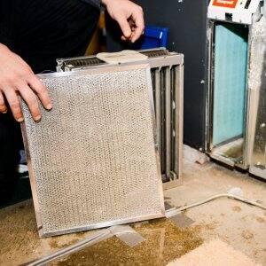 hand holding HVAC filter next to furnace