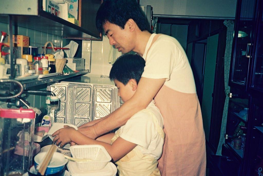 幼い息子が食器を洗うのを後ろから手伝う父