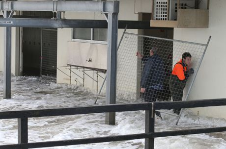 Workers put up fencing on the Kerferd Road Pier club house in Melbourne after waves from Port Phillip Bay blew out the doors, Tuesday, June 24, 2014. Extreme weather with strong winds has been hitting Melbourne and parts of Victoria.