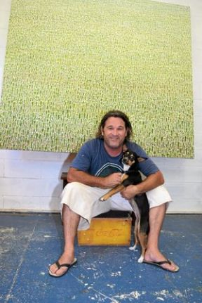 FIELD OF DREAMS: Artist Rob Ryan along with his CAWI rescue dog, Kandi, in front of the large puiture of Belongil in its undisturbed state. Photo Christian Morrow / Byron Shire News