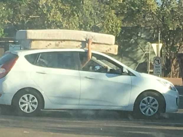 Two Mattresses Balance On The Roof Of A Car Held To By Driver