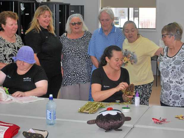CRAFTY: Lisa (aka Karisma) shows her Christmas pine cone decorating skills as Lyne, Regina, Rachelle, Mary, Heather and Shirley look on and Tracey (far left) gets on with other work.