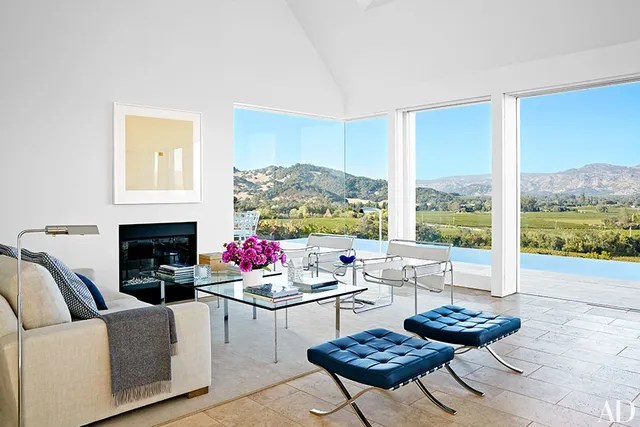 Designed by Jacobsen Architecture and dubbed Birdhouse, the weekend home of Jeff Atlas overlooks vineyards in California's Napa Valley. Knoll furnishings mingle in the living area, including Marcel Breuer chairs and Mies van der Rohe cocktail tables and stools; the artwork is by Gene Davis, the sofa is by RH, and the rug is by Stark.
