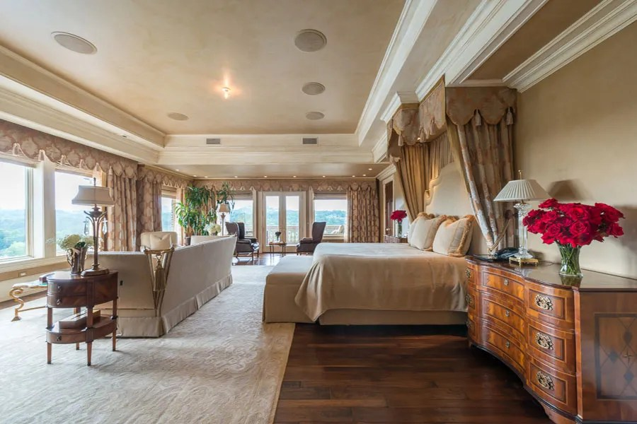 Set in a private wing, the spacious master suite is lined with windows overlooking the lush property.