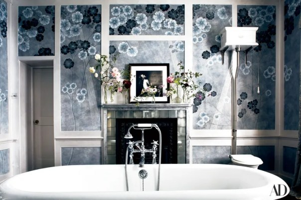 De Gournay's hand-painted Anemones on custom Xuan paper in dusk covers her master bath, where an Irving Penn portrait of the model sits above a mirrored-and-stone hearth, behind a claw-foot tub by Drummonds. Wall coverings: $1,470 per 3' wide panel.