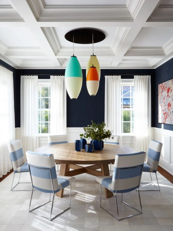 """""""A round table in a square room feels so right,"""" says Brown of the custom table from Robert Stilin Shop, which is topped with repurposed tractor gears from Huniford Design. A nod to retro fishing floats, the chandelier combines three vintage lights by Heifetz Rotoflex with a custom plate from Stellar Union, in Southampton."""