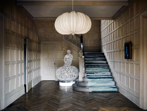 In order to add in some light and modernity to the very traditional front foyer, Thomas worked with woodworker Willem Raké, who kept the original millwork but had it sanded and whitewashed using a complex three-step lime wash. The runner on the stairs is from Holland and Sherry, the sculpture,