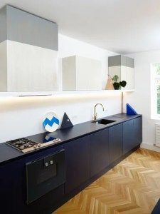 The Case For Installing Richlite Countertops  They re Made of Paper     Modern kitchen with black cabinets and Richlite countertops and chevron  wood floor