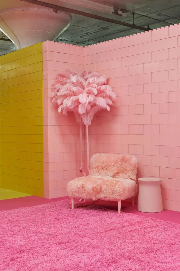 pink room with pink palm tree, pink rug, and fuzzy pink chair, next to yellow room