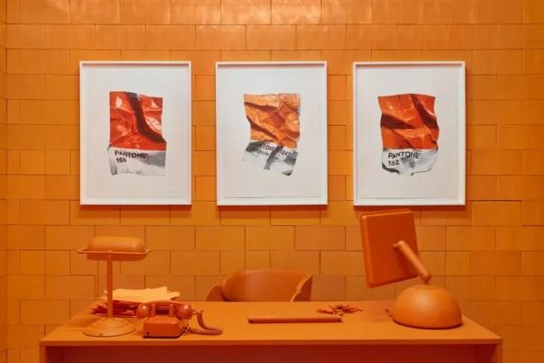 orange home office featuring orange chair, orange computer, art, and desk lamp
