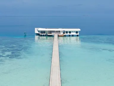 a long boardwalk leads to a white villa in the clear ocean
