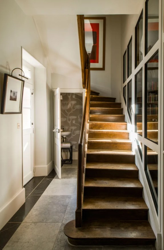 Belgian gray stone floors and the original staircase. Basmajian replaced one of the walls with glass panels to let the...