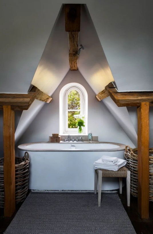 Under the only dormer in the house and with a great view out the little window an extra deep tub with a stone surround....