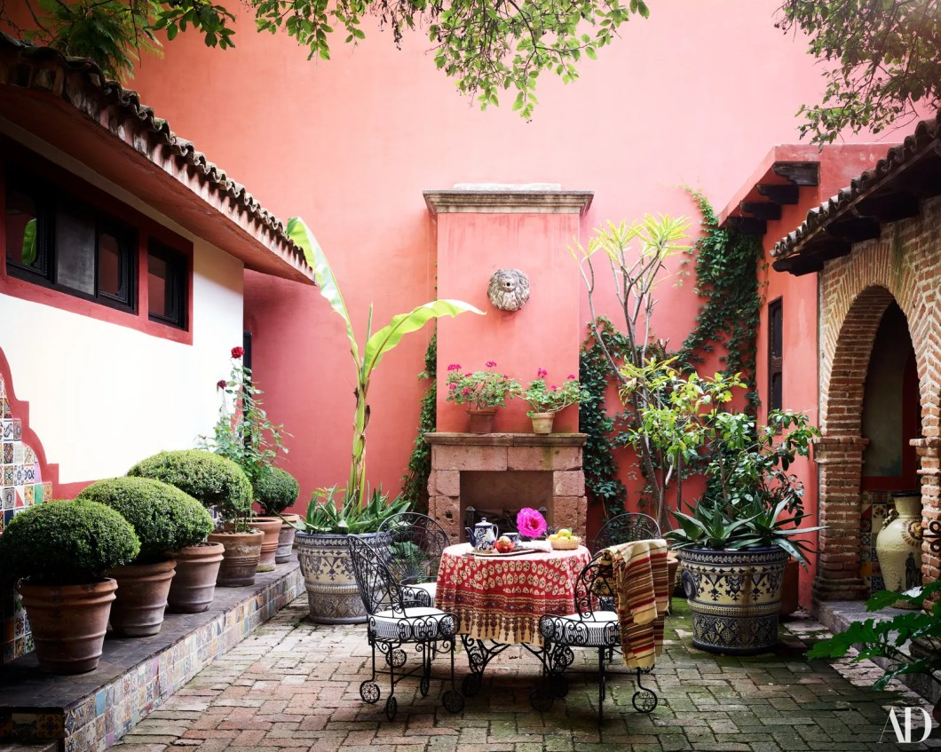 A 1940s Mexican wroughtiron table and chairs stand in a courtyard. Tablecloth by Simrane custom largescale planter from...
