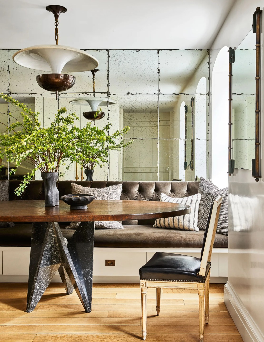 Custom mirrors by TG Glass works line a wall in the dining area where the table has a 1980's Italian base and a custom...