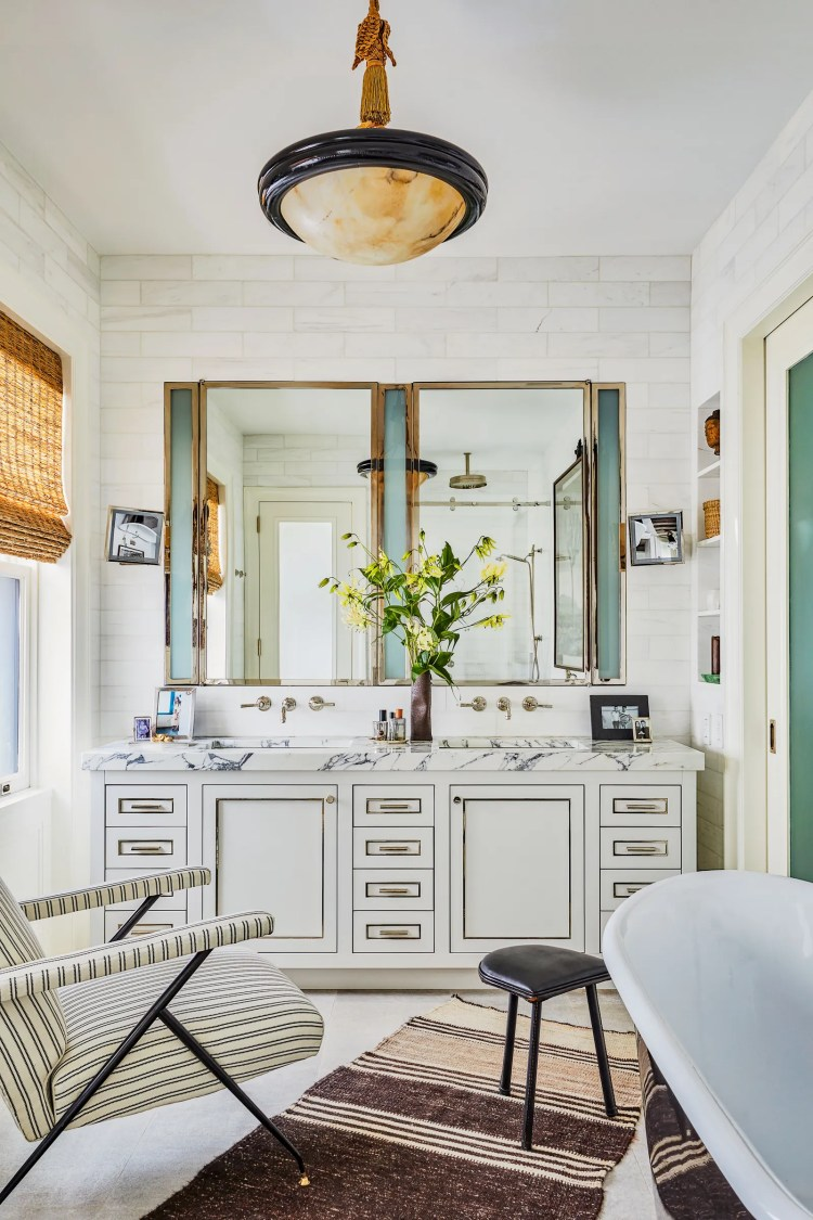 A 19thcentury Alabaster pendant crown the master bath. The vintage armchair wears a Schumacher cotton Jacques Adnet stool.