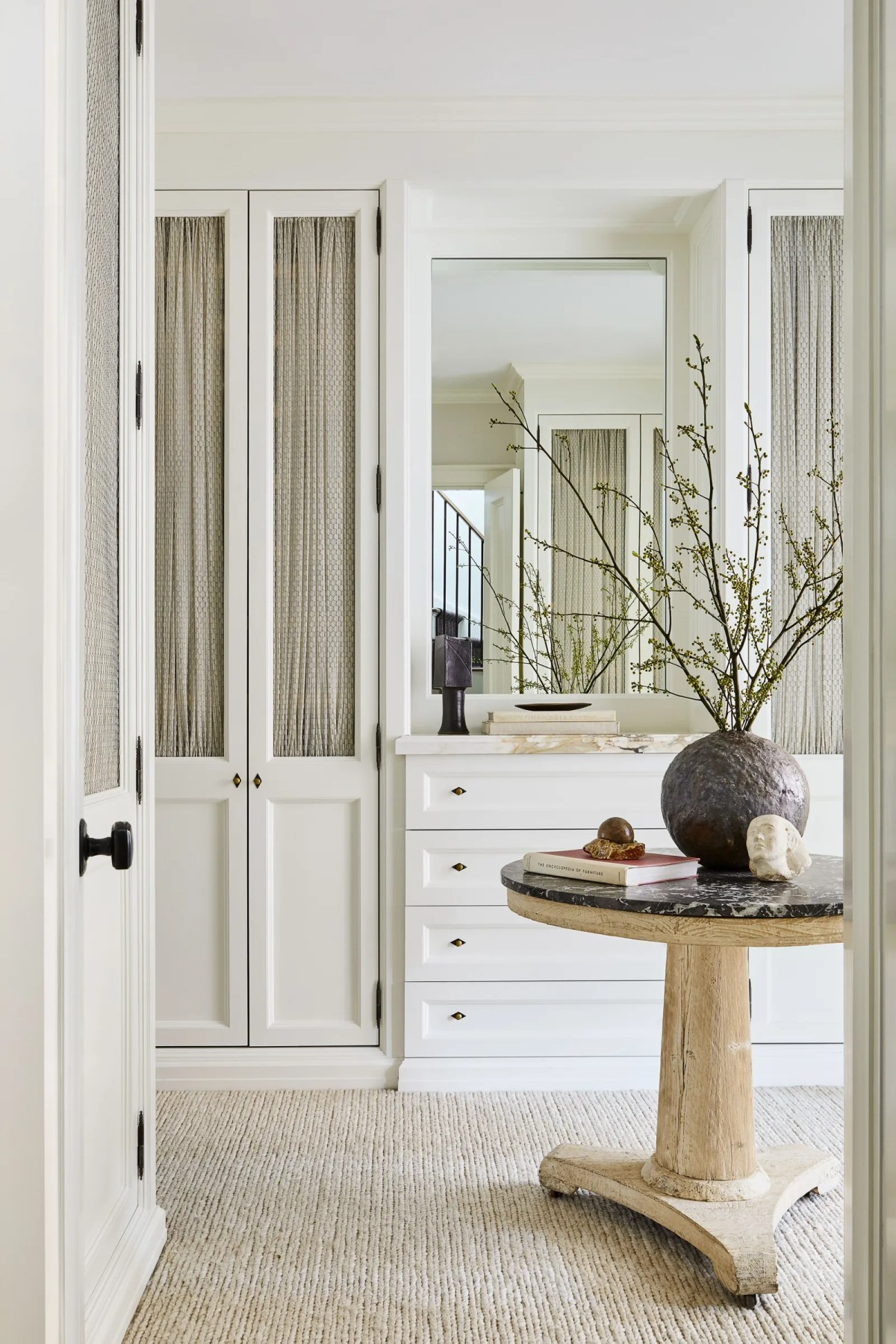 The master dressing room features custom cabinetry by Hetman. Vase by Casey Zablocki atop a 19thcentury French table.