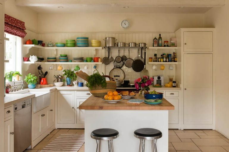 pBarstools and a butcher's island in a white kitchen with colorful crockeryp