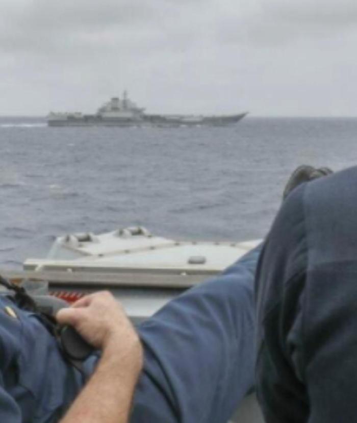 美国海军舰长布里格斯中校在船侧举起了脚。
