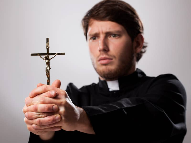 Priest holding a crucifix in front of him