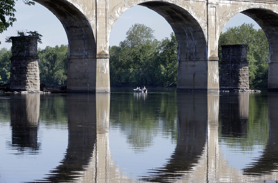 People fish from a boat near a bridge on the Delaware River, Sunday, May 24, 2015, in the West Trenton section of Ewing Township, N.J. (AP Photo/Mel Evans)