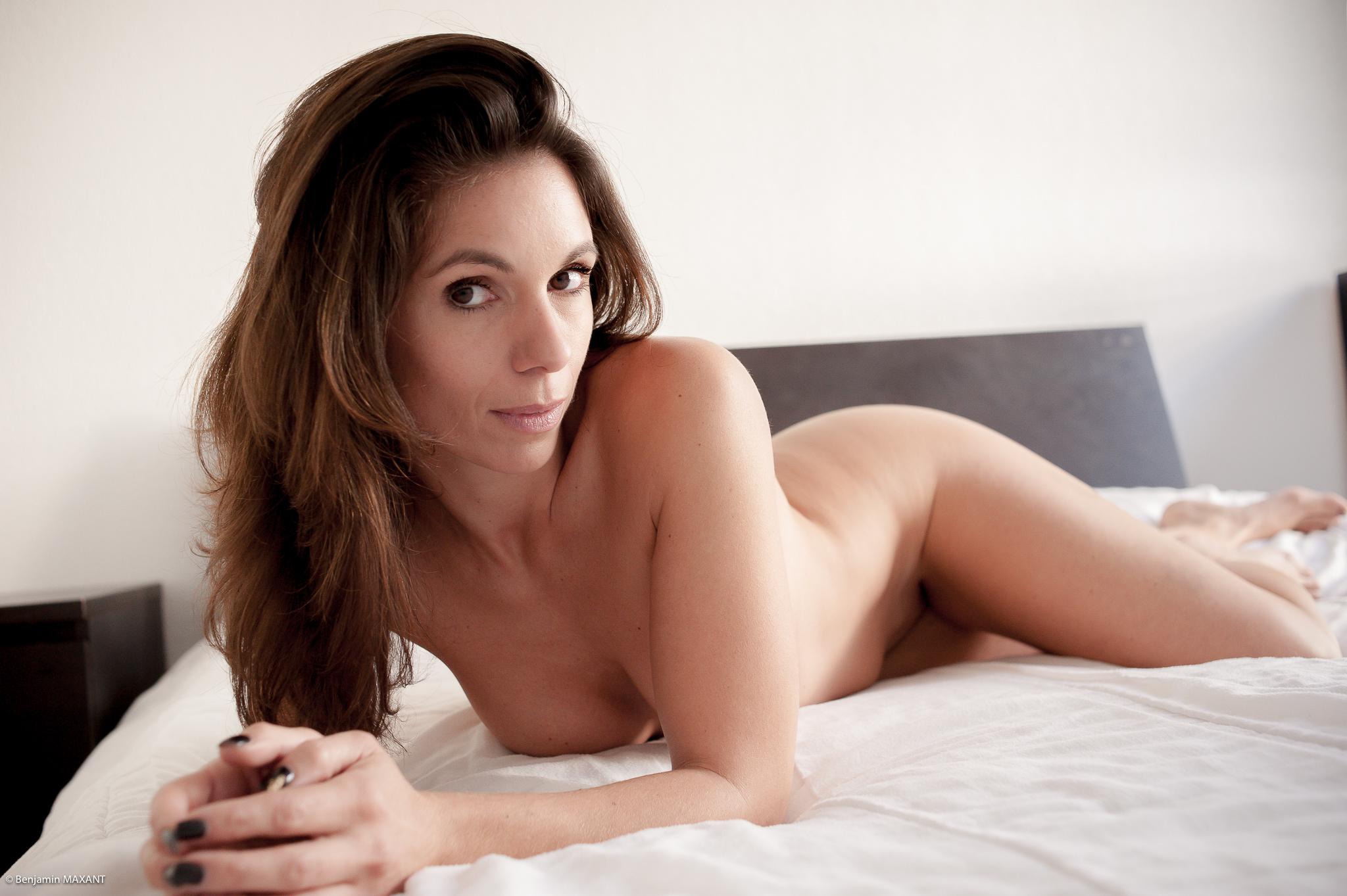Séance photo nu en intérieur sur un lit avec une lumière naturelle