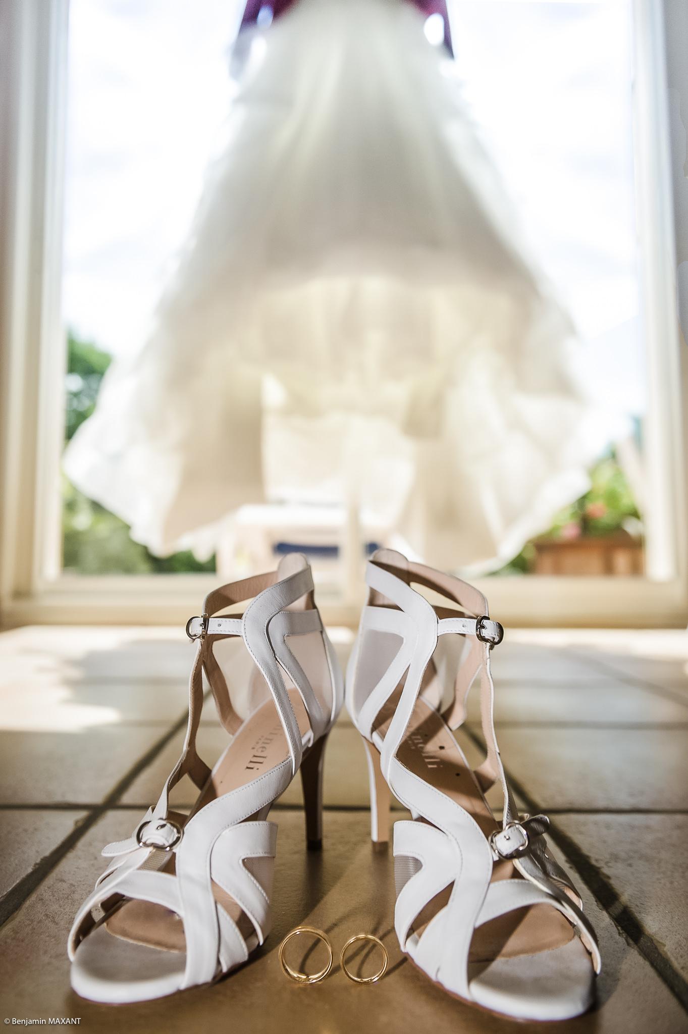 Les chaussure de la mariée avec les alliances au milieu et la robe de mariée dans le fond