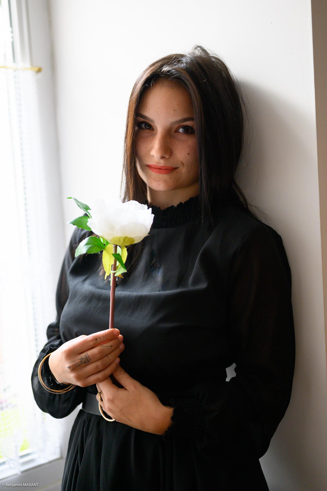Séance photo boudoir robe noire adosées contre le mur tenant une fleur dans les mains