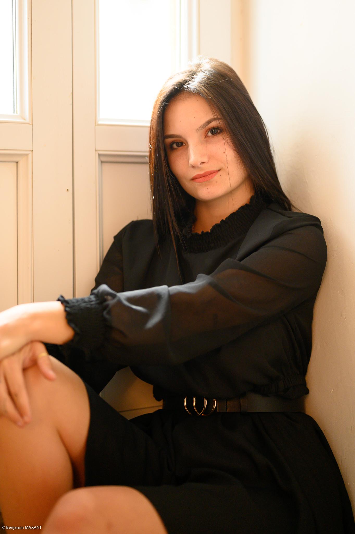 Séance photo boudoir robe noire assise près de la porte